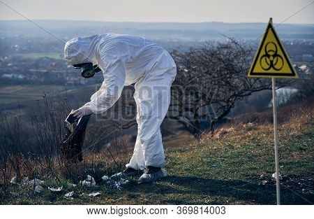 Environmentalist Wearing White Protective Coverall, Gas Mask, Collecting Garbage Into Black Waste Ba