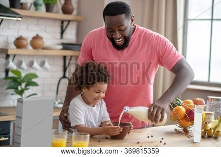 African American Bearded Man Standing And Pouring Milk In His Daughters Plate