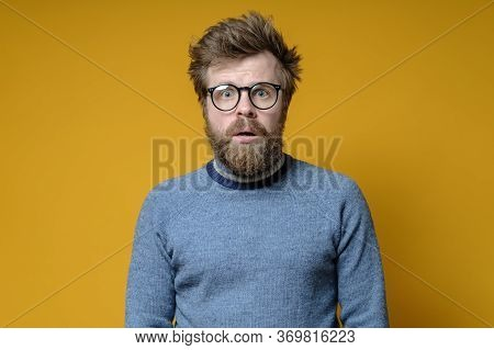 Excited Shaggy Man With Glasses And An Old Sweater Looks At The Camera With A Shocked Expression On