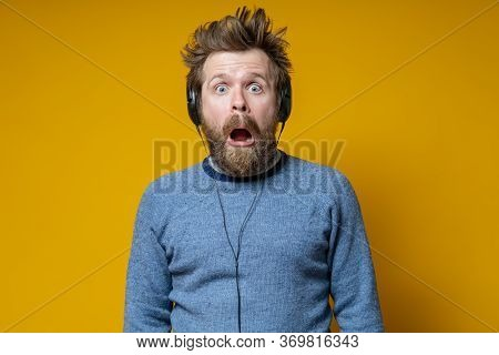 Man In The Headphones Is Shocked. Shaggy Music Lover In An Old Sweater Fearfully Looks With His Mout