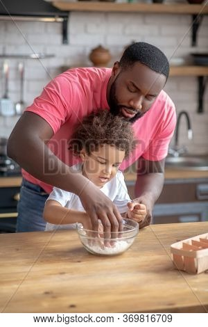 Cute Kid With Curly Hair Looking Involved Putting Her Hands Into The Bowl With Flower