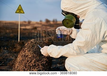 Environmentalist Doing Laboratory Test In Field After Fire, Wearing Protective Suit, Gas Mask, Study