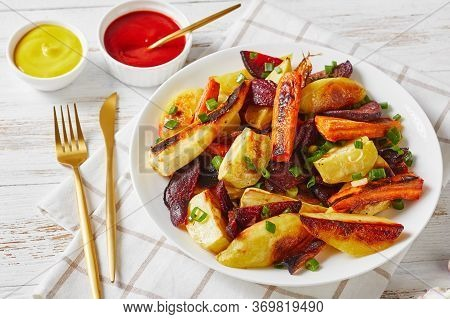 Close-up Of Grilled Veggies, Beetroot, Potato Wedges, Parsnips, Carrots Sprinkled With Chopped Green
