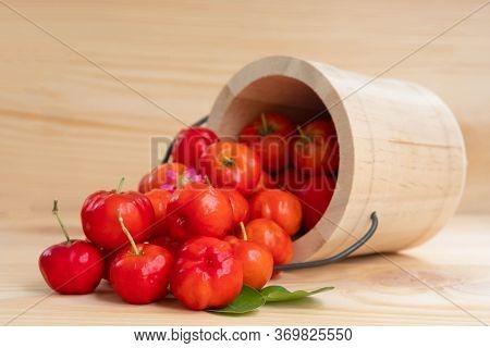 Acerola Cherry In Wooden Bucket On Wooden Background. Select  Focus, Barbados Cherry, Malpighia Emar