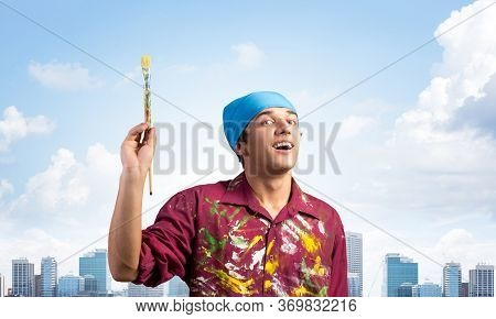 Smiling Young Painter Artist Pointing Upwards With Paintbrush In Hand. Portrait Of Happy Painter On