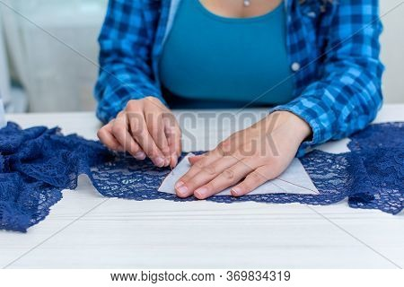 A Cheerful Seamstress In A Blue Checked Shirt Is Working In Her Workshop. Close-up, On A Table Next