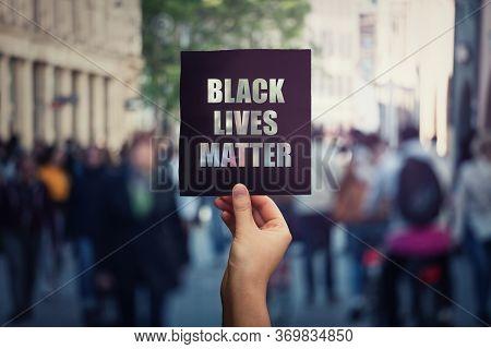 Black Lives Matter, Street Demonstration. Human Hand Holds A Dark Protest Banner, Against Injustice.