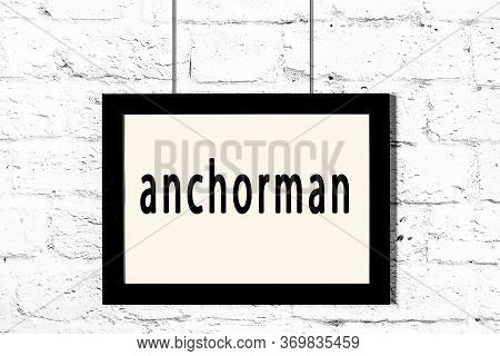 Black Wooden Frame With Inscription Anchorman Hanging On White Brick Wall