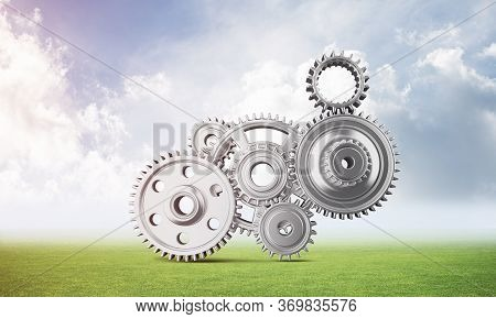Abstract Mechanism With Cogwheels On Green Meadow. Construction And Manufacturing. Mechanical Techno