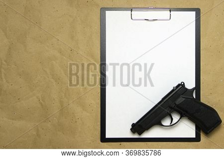 A Tablet With A White Sheet Of A4 Format With Gun On A Beige Craft Paper. Concept Of The Legal Syste