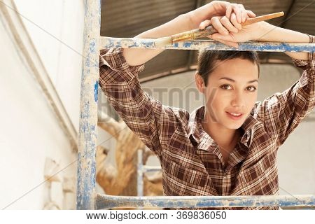 Female interior decorator leaning on Scaffolding portrait