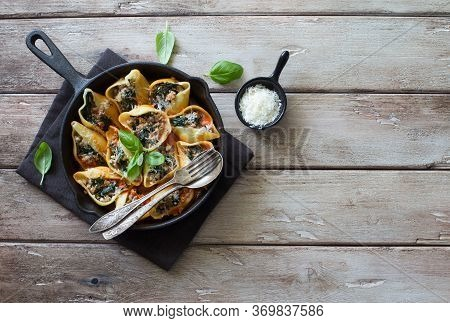 Conchiglioni Stuffed With Meat And Spinach Served In A Skillet On  Natural Wooden Background. Flat L
