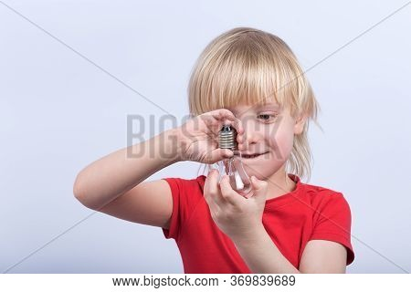 Fair-haired Boy Playing With Light Bulb. Child Holding Incandescent Lamp.