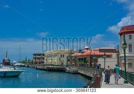 Bridgetown, Barbados, Caribbean - 22 Sept 2018: Couple Walking Along The Promenade At Marina Bay Of