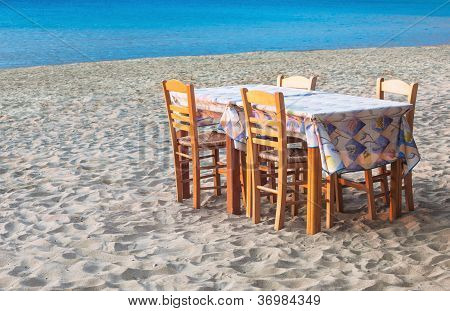Greek Taverna Table And Chairs On Sandy Beach