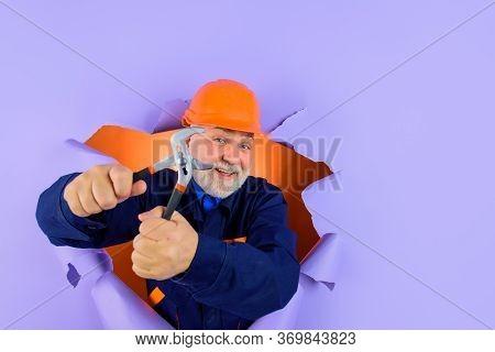 Worker Or Builder In Helmet With Pliers Looking Through Paper. Professional Plumber Holds Pliers. Au