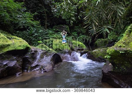 Young Caucasian Woman Sitting On The Rock Near The River In Vajrasana Or Diamond Pose. Hands Raising