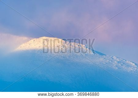 Snow Capped Mountain Peak Disappears Into The Clouds Creating A Beautiful Painterly View Of Unspoile