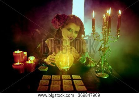 Magnificent fortune teller woman reading future on magical crystal ball and tarot cards.