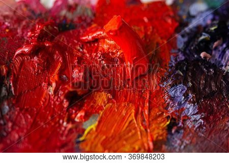 Red Oil Paint On The Artist's Palette. Hobbies And Leisure: Mixing Paints. Top View Of The Palette.