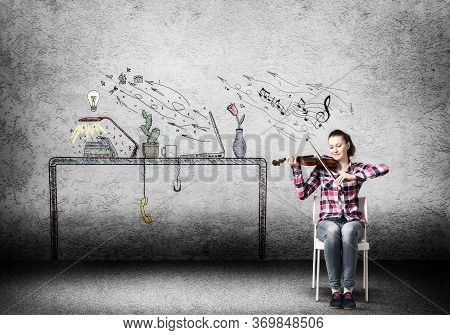 Young Happy Woman Playing Violin In Room. Creative Girl Sitting On Chair And Practicing With Violin.