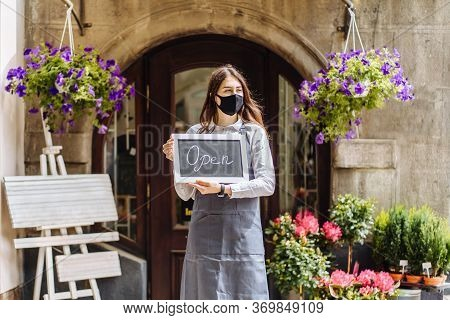 Business Owner Woman Wear Protective Face Mask Holding Open Sign At Her Floral Shop Outdoor, Open Ag