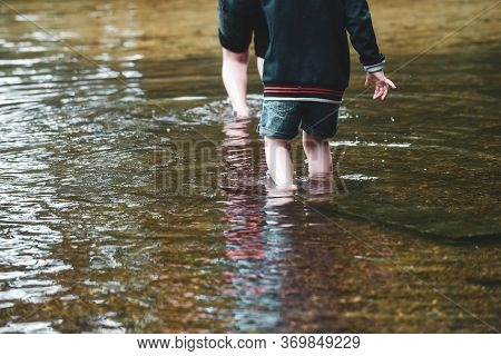Children Playing Outside In A Shallow Stream Paddling In The Water