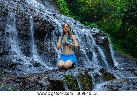 Yoga Pose. Young Caucasian Woman Sitting On The Rock, Meditating, Practicing Yoga At Waterfall. Vajr