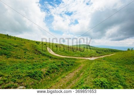 Path Through Mountain Landscape. Road Through Green Rolling Hills. Cloudy Weather