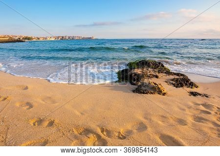 Sandy Beach With Rocks. Sunny Morning In The Resort Town. Wave Brings Seaweed On The Stones On The S