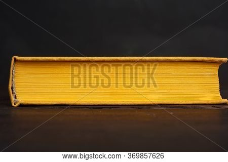 Book In Yellow Hardcover Against A Black Chalk Board, Close Up