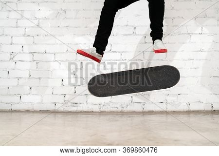 Skateboarder Performing Skateboard Trick - Kick Flip On Concrete. Olympic Athlete Practicing Jump On