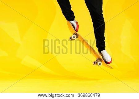 Skateboarder Performing Skateboard Trick - Ollie On Concrete. Studio Shot Of Olympic Athlete Practic