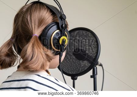 Closeup Of Teenager Recording Music In Home Studio. Girl With Headphones And Microphone Recording So