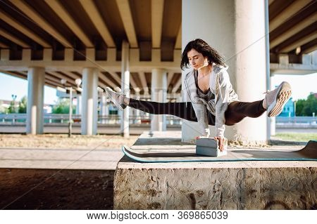 Stretching Gymnast Or Dancer Woman Doing Stretching Exercises With A Urban View Under The Bridge. Sl