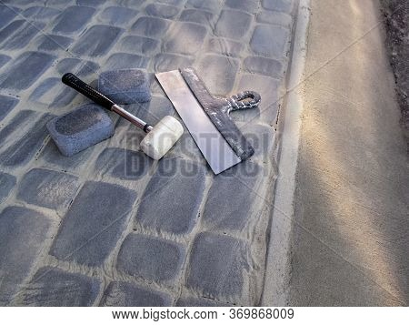 White Rubber Mallet And A Large Construction Spatula Lie On The Surface Of A Newly Laid Gray Paving