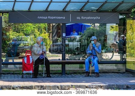 Uzhgorod, Ukraine - June 3, 2020: Elderly People In Protective Masks/gloves Are Talking While Sittin