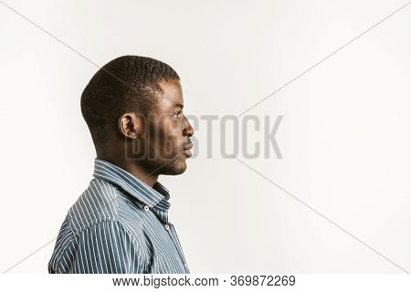 Young African Man On White Background. Profile View Of Serious Afro American Student Or Businessman