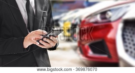 Businessman Using Smartphone On Blurred Background Of New Car Displayed In Showroom Dealer With Copy