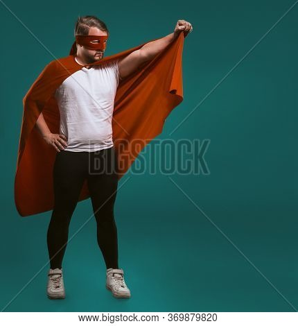 Super Hero Savior Man Ready To Fly. Legendary Brave Man In Red Mask Holds His Cloak Ready To Save Wo