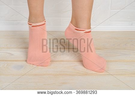 Woman Feet In Short Pink Cotton Socks Standing On Toes On A White Wood Floor. Stand On Tiptoe In Low