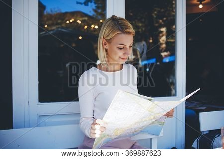 Charming Hipster Girl Examines Geographical Atlas While Sitting In Modern Sidewalk Cafe In Summer Da