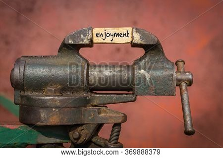 Concept Of Dealing With Problem. Vice Grip Tool Squeezing A Plank With The Word Enjoyment