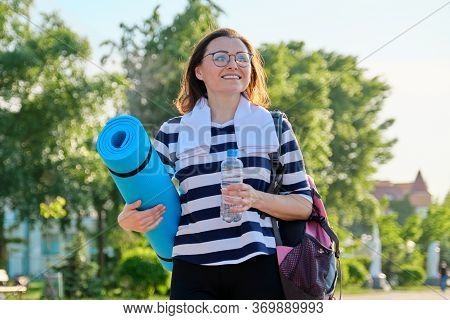 Outdoor Happy Mature Woman Walking After Fit Exercises In The Park, With Backpack, Yoga Mat. Active