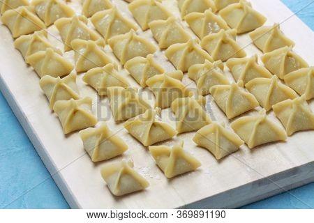 handmade manti (turkish ravioli type dumplings) on wooden cutting board, before cooking