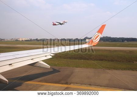 Sao Paulo, Brazil - October 12, 2014: Tam Airlines Taking Off Seen From Gol Airline At Guarulhos Air