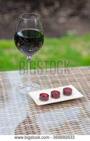 Glass Of Red Wine And Marmalade Wine Candies On The Table. Homemade Marmalade.