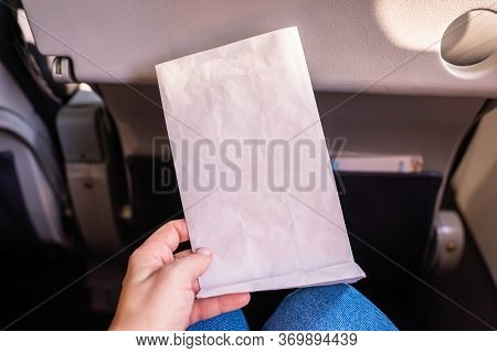 Air Sickness Paper Bag In The Hand Of Nauseous Passenger During Flight In The Airplane.