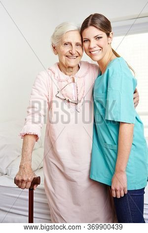Smiling elderly nurse stands with a happy elderly woman in a nursing home
