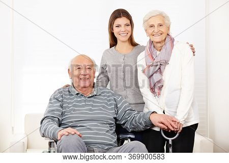 Smiling nurse at home with an old elderly couple